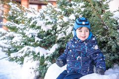 Funny little kid boy in colorful clothes playing outdoors during snowfall. Active leisure with children in winter on cold snowy da. Ys. Happy child having fun Royalty Free Stock Images