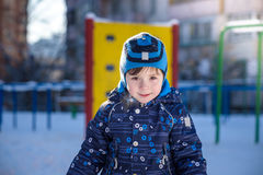 Funny little kid boy in colorful clothes playing outdoors during snowfall. Active leisure with children in winter on cold snowy da Stock Photo
