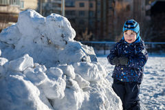 Funny little kid boy in colorful clothes playing outdoors during snowfall. Active leisure with children in winter on cold snowy da Royalty Free Stock Photo