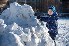 Funny little kid boy in colorful clothes playing outdoors during snowfall. Active leisure with children in winter on cold snowy da Stock Photography