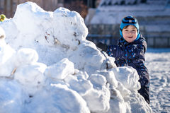 Funny little kid boy in colorful clothes playing outdoors during snowfall. Active leisure with children in winter on cold snowy da Stock Images