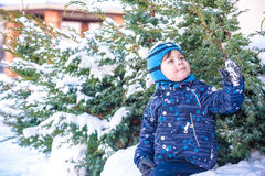 Funny little kid boy in colorful clothes playing outdoors during snowfall. Active leisure with children in winter on cold snowy da Royalty Free Stock Image