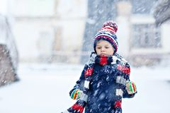 Funny little kid boy in colorful clothes playing outdoors during strong snowfall Stock Images