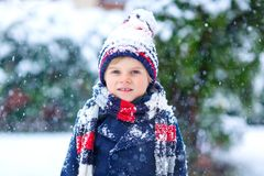 Funny little kid boy in colorful clothes playing outdoors during strong snowfall Stock Image