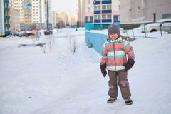 Funny little kid boy in colorful clothes playing outdoors in winter on cold snowy days. Happy child having fun and. Playing with snow Royalty Free Stock Photos