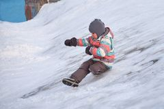 Funny little kid boy in colorful clothes playing outdoors in winter on cold snowy days. Happy child having fun and. Playing with snow Stock Images