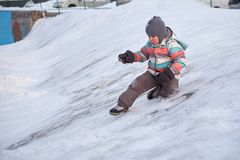 Funny little kid boy in colorful clothes playing outdoors in winter on cold snowy days. Happy child having fun and. Playing with snow Royalty Free Stock Image