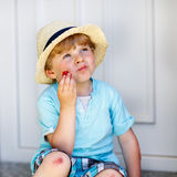 Funny little kid boy eating fresh organic strawberries Royalty Free Stock Images