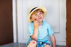 Funny little kid boy eating fresh organic strawberries Stock Photos