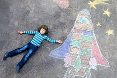 Little kid boy flying by a space shuttle chalks picture. Funny little kid boy flying in universe by a space shuttle picture painting with colorful chalks Royalty Free Stock Photos