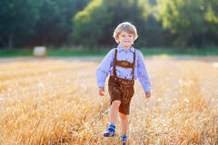 Funny little kid boy in leather shors, walking  through wheat fi Stock Image