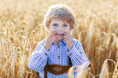 Funny little kid boy in leather shors, walking  through wheat fi Royalty Free Stock Image