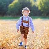 Funny little kid boy in leather shors, walking  through wheat fi Stock Photos