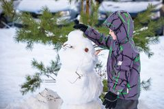 Funny little kid boy making a snowman and eating carrot, playing having fun with snow, outdoors on cold day. Active leisure childr Royalty Free Stock Photo