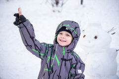 Funny little kid boy making a snowman and eating carrot, playing having fun with snow, outdoors on cold day. Active leisure childr Stock Photos