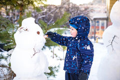 Funny little kid boy making a snowman and eating carrot, playing having fun with snow, outdoors on cold day. Active leisure childr Stock Image