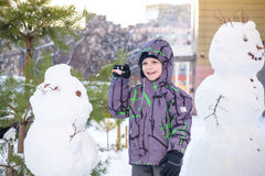 Funny little kid boy making a snowman and eating carrot, playing having fun with snow, outdoors on cold day. Active leisure childr Royalty Free Stock Photos