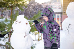 Funny little kid boy making a snowman and eating carrot, playing having fun with snow, outdoors on cold day. Active leisure childr Stock Photo