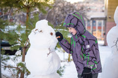 Funny little kid boy making a snowman and eating carrot, playing having fun with snow, outdoors on cold day. Active leisure childr Royalty Free Stock Photography