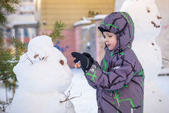 Funny little kid boy making a snowman and eating carrot, playing having fun with snow, outdoors on cold day. Active leisure childr Royalty Free Stock Image