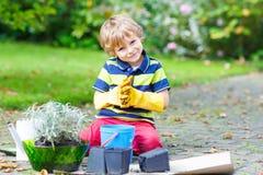 Funny little kid boy planting flowers in garden on sprinig Stock Images
