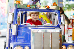 Funny little kid boy riding on a merry-go-round carousel Royalty Free Stock Photos