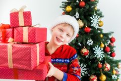 Funny little kid dressed in red night pajamas and hat of santa Stock Image
