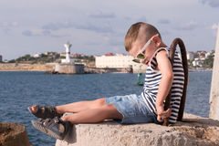 Funny little kid in sunglasses and singlet sitting on breakwater on the sea background Royalty Free Stock Photo