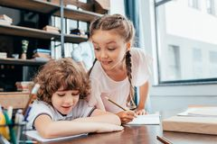 Funny little kids doing. Homework together royalty free stock photos
