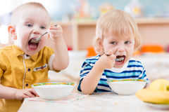 Funny little kids eating from plates in kindergarten. Funny kids eating in kindergarten Stock Photo