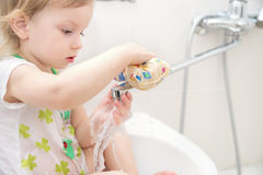 Funny little little girl sitting in the sink and wash water faucet, playing with water drops and splashes. Stock Images