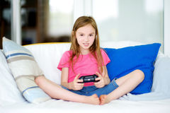 Funny little preteen girl playing with game console Stock Images