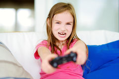 Funny little preteen girl playing with game console Royalty Free Stock Photos