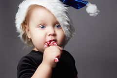 Funny child. little santa. happy kid with lollipop candy Royalty Free Stock Images