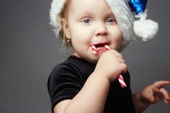 Funny little santa girl. happy kid with lollipop candy Stock Image