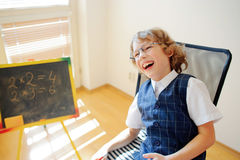 Funny little schoolboy in glasses cheerfully laughs. Stock Image