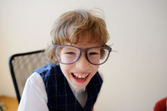 Funny little schoolboy in huge glasses carelessly laughing. Stock Photo