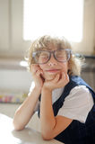 Funny little schoolboy in huge glasses has fallen into a reverie. Stock Photography