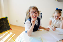 Funny little schoolchildren in glasses, boy and girl, sit at one desk. Royalty Free Stock Image