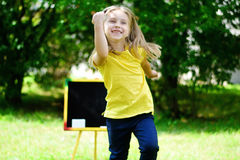 Funny little schoolgirl feeling excited about going back to scho. Ol, outdoor Royalty Free Stock Image