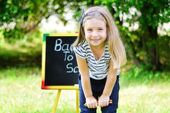Funny little schoolgirl feeling excited about going back to school. Little schoolgirl feeling excited about going back to school Royalty Free Stock Image