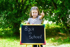 Funny little schoolgirl feeling excited about going back to school.  Royalty Free Stock Image