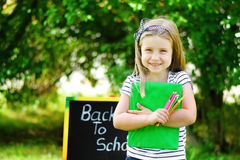 Funny little schoolgirl feeling excited about going back to school.  Stock Photo