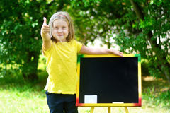 Funny little schoolgirl feeling excited about going back to school. Blackboard Royalty Free Stock Images
