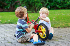 Funny little sibling  boys repairing bicycle wheel Stock Images