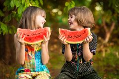 Funny little sisters girl eats watermelon in summer. Healthy eating concept stock photos