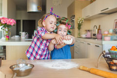 Funny little sisters learn to sculpt a dough on a kitchen Royalty Free Stock Images