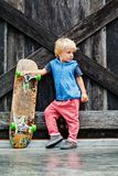 Funny little skater with skateboard before lesson Stock Photography