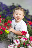 Funny little smiling boy sitting with toy shovel on flower bed on warm sunny day. Outdoors. Environment concept. Stock Image