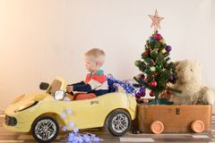 Funny little smiling kids driving toy car with Christmas tree. Happy child in colour fashion clothes bringing hewed xmas tree from. Snowy forest. Boys having royalty free stock photography